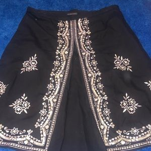 Gently used black skirt w/ white stitched design.